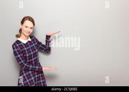 Studio Portrait von glücklich ziemlich blonde Mädchen tragen karierte Kleid, fröhlich lächelnd, zeigt Größe von etwas groß mit Händen, mit Platz für Ihre