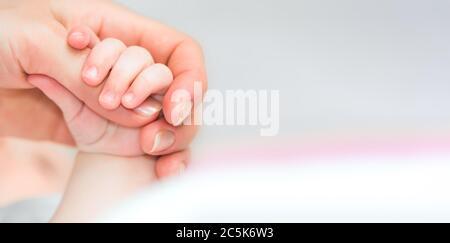 Nahaufnahme der Hand des Babys, die den Finger der Mutter mit Zärtlichkeit und Kopierraum hält - Stockfoto