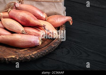 Zwiebelschalotte auf schwarzem, dunklem Hintergrund. Essen Gemüse und gesund essen. Essen Schalotten, Zugabe zu verschiedenen Gerichten, diversifizieren Lebensmittel.