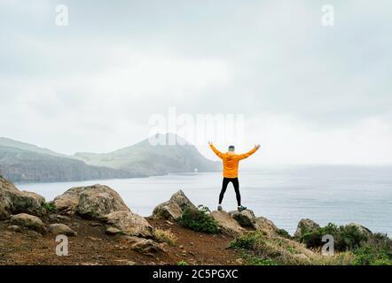 Trail Runner Mann gekleidet orange wasserdichte Jacke, Laufstrumpfhose und Schuhe genießen Atlantik Bucht Blick auf Ponta de Sao Lourenço Halbinsel -die e