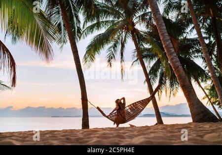Junge Frau, die in Hängematte auf dem exotischen Insel Sandstrand bei Sonnenaufgang schaukelt - Stockfoto