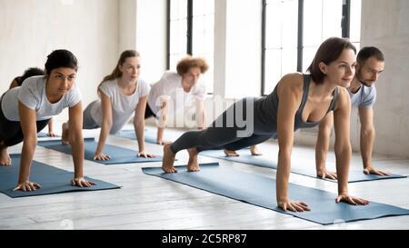 Fokussierte Menschen üben barfuß Yoga auf Matte. - Stockfoto