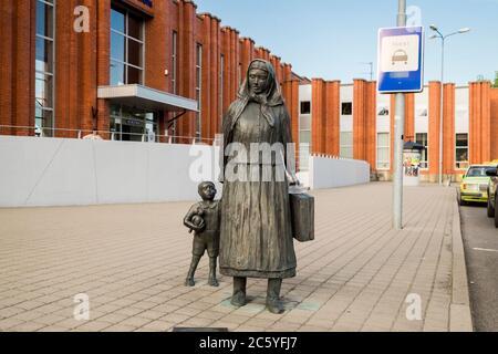 Eine Bronzeskulptur einer armen bäuerlichen Frau, die mit ihrem Sohn unterwegs ist. Vor dem Bahnhof in Klaipėda, Litauen. - Stockfoto