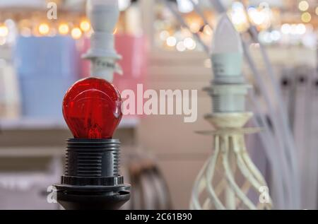 Rote Energiesparlampe in schwarzer Patrone. - Stockfoto