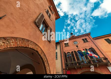 Altes historisches Haus und Rathaus mit Balkon, Fahnen und Uhr unter schönem Himmel in Alba, Piemont, Norditalien (Low-Angle-Ansicht).