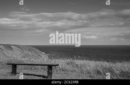 Eine Holzbank befindet sich auf einer Klippe mit Blick auf das Meer. Eine Landzunge ragt nach außen und ein blauer Himmel mit Wolken ist oben. - Stockfoto