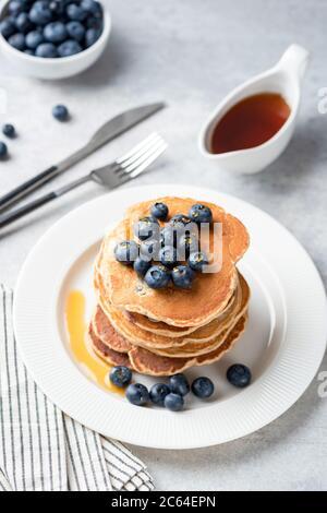 Pfannkuchen mit Heidelbeeren und Ahornsirup auf weißem Teller, grauer Betontischhintergrund. Vertikale Ausrichtung. Leckere Pfannkuchen zum Frühstück - Stockfoto