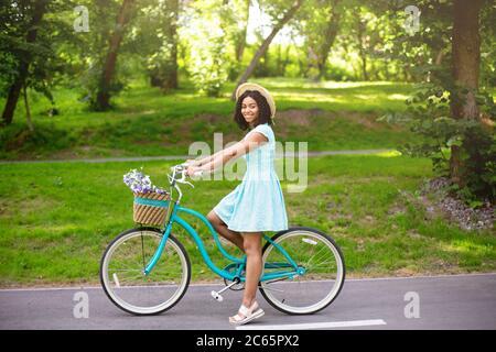 Portrait von attraktiven afroamerikanischen Mädchen mit Fahrrad im Park am Sommertag - Stockfoto