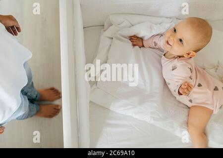 Glückliches Baby im Bett und Mütter Beine. Zu Hause, helle Innenausstattung.