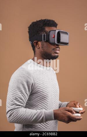 Dunkelhäutige tausendjährigen Tourist in Freizeitkleidung mit Brille mit Head-mounted display für Smart Phone, die mit Steuerungen in Händen, doi - Stockfoto