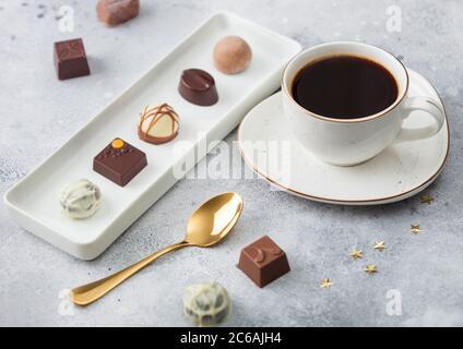 Luxus Schokolade Bonbons in weißem Porzellan Teller mit Tasse schwarzen Kaffee und goldenen Löffel auf hellen Hintergrund. - Stockfoto