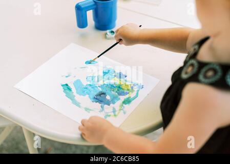 Kleinkind malen mit Aquarellen draußen auf der Terrasse Stockfoto