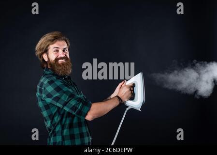 Häusliche tägliche Arbeit. Mann zu Hause bügeln. Happy man Bügelkleidung. Mann konzentriert sich auf das Bügeln eines Hemdes. Waschküche zu Hause. Kleidung Bügelbrett Haushaltskonzept. - Stockfoto
