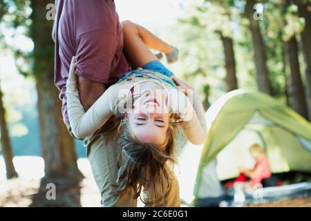 Vater trägt glückliche Tochter außerhalb Zelt in Wäldern - Stockfoto