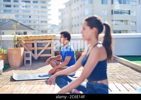 Junge Männer und Frauen üben Yoga auf sonnigem städtischen Dach - Stockfoto