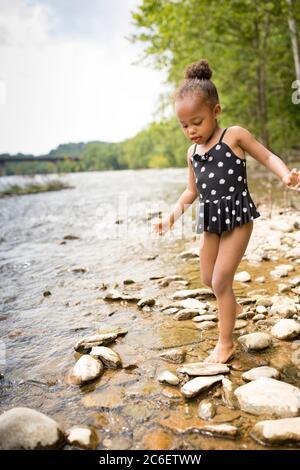 Ein junges Mädchen aus gemischter Rasse wadet im flachen Wasser des Shenandoah River bei Harpers Ferry, West Virginia, USA. - Stockfoto