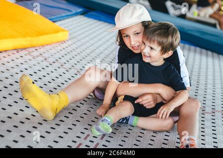 Lustige lächelnde Kinder auf dem Trampolin. Älterer Bruder umarmt jünger. Aktive Erholung im Sportzentrum. Zwei glückliche Emotionen Jungen, Brüder spielen und