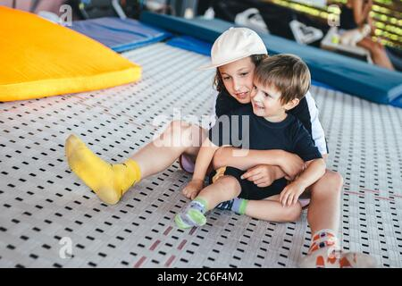 Zwei kaukasische Brüder Jungen genießen es, auf einem Trampolin in einer Umarmung zu sitzen. Kinder spielen zusammen auf einem Trampolin in einem Sportzentrum. Fitnessraum im Freien