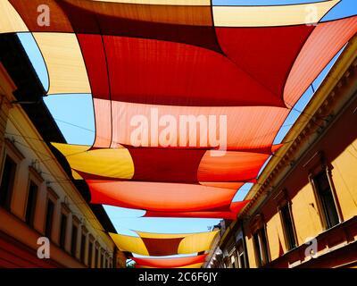 Bunte dicht gewobene Markise & Zelt Sonne Segel UV-Schutz Stoff von außen über der städtischen Straße aufgehängt. Altstadt Innenstadt. Sonnenschutz