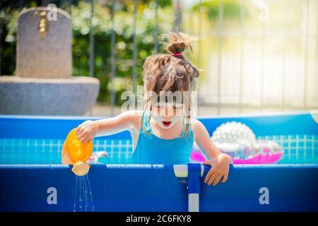 Kleines kaukasisches Mädchen, in einem blauen Schwimmbad, spielt mit einer Spielzeugkippe an einem hellen Sommertag. Globale Erwärmung oder heiße Temperatur Effekt Stockfoto
