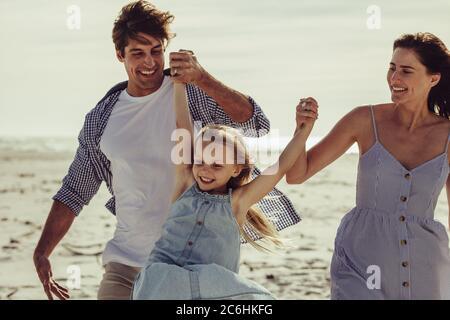Paar hält die Hände ihrer Tochter und spielt am Strand. Mädchen mit einer tollen Zeit mit Eltern auf einem Urlaub.