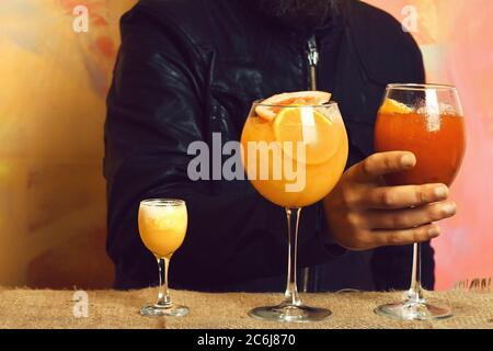 Männliche Hand des kaukasischen Mannes, der ein Glas alkoholisches Getränk oder frische Cocktails hält, mit Schuss in Rock Black auf farbenfrohem Texture Studio Hintergrund - Stockfoto