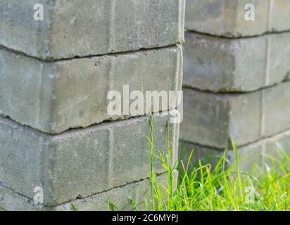 Haufen von Pflaster grauen Ziegel auf grünem Gras - Stockfoto