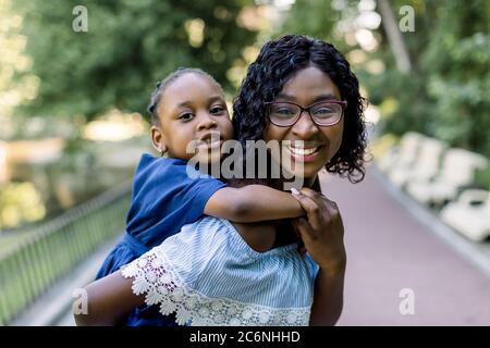 Nette kleine afrikanische Mädchen Tochter auf einem Piggy-Rücken Fahrt mit ihrer charmanten lächelnden Mutter, zu Fuß im Stadtpark mit grünen Bäumen. Nahaufnahme Porträt eines Stockfoto
