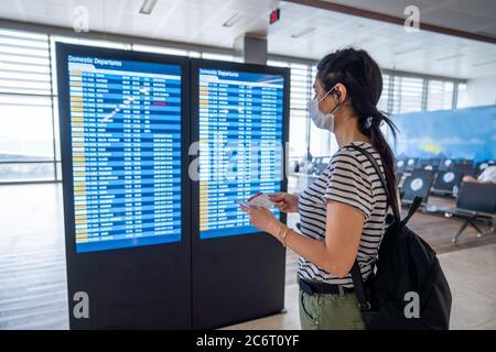 Junge Frau in Virenschutz Gesichtsmaske Blick auf Informationstafel im Flughafen. Corona Virus bricht aus. Hochwertige Fotos - Stockfoto