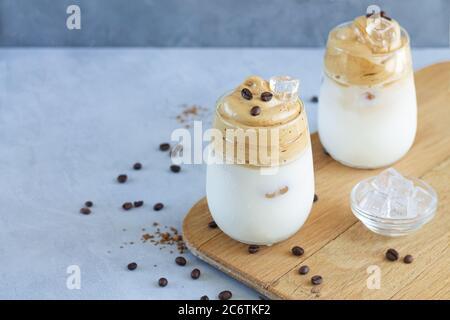 Zwei Gläser kalten Dalgona Kaffee mit Eiswürfeln auf Holzbrett mit Platz für Ihren Text - Stockfoto