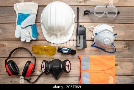 Arbeitsschutzausrüstung flach legen. Industrielle Schutzausrüstung auf Holzhintergrund. Baustellen-Gesundheits- und Sicherheitskonzept. Stockfoto