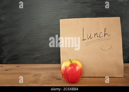 Umweltfreundliche braune Papier-Lunchtasche auf Holztisch mit rotem Apfel. Kreidetafel auf dem Hintergrund. Zurück zur Schule Konzept. - Stockfoto