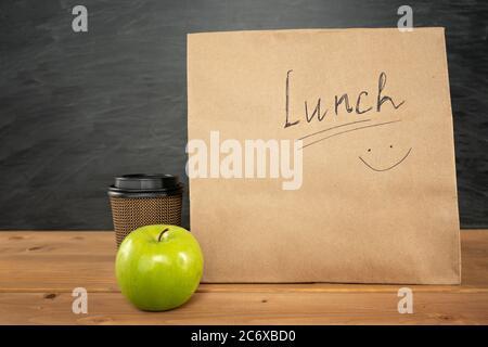 Umweltfreundliche braune Papier-Lunchtasche auf Holztisch mit Apfel und Kaffeetasse. Kreidetafel auf dem Hintergrund. Zurück zur Schule Konzept. - Stockfoto