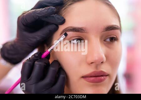 Schöne junge Frau bekommt Augenbraue Korrektur Verfahren. Junge Frau malt ihre Augenbrauen in Beauty Salon. - Stockfoto