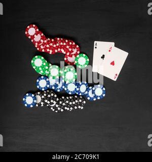 Zwei Karten Asse und Chips, Pokerspiel. Schwarzer Hintergrund, Draufsicht. - Stockfoto