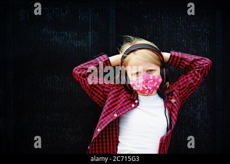 Kleines positives Kind in Kopfhörern Musik hören mit Spaß heben die Hände hoch. Lustige Mädchen tragen stilvolle Schutz Gesichtsmaske durch Coronavirus COVID 19 - Stockfoto