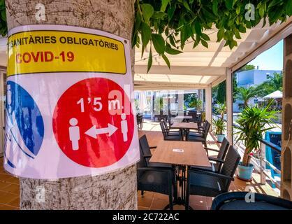 Hinweis auf die kommende allgemeine Maskenpflicht und leere Tische und geschlossene Geschäfte im ehemals gut besuchten Ferienort Cala d'Or im Südosten von CO - Stockfoto