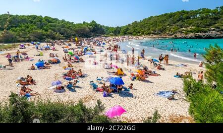 Einsamer Strand im Parc Natural de Mondrago und Strand S'amador mit zahlreichen Badegäste, die in der Regel halten den Mindestabstand während der Corona pandemi - Stockfoto