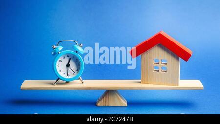Eine Uhr und ein Miniaturhaus auf der Waage. Hypothek- und Darlehenskonzept. Immobilien und Risiken. Sachversicherung. Kredit. Steuerzahlung. Dienstprogramme. Nachteile Stockfoto