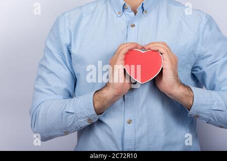 Männliche Hände halten rote Box in Form von Herz. Geschenk für Geliebte. Geschenk zum Valentinstag. - Stockfoto