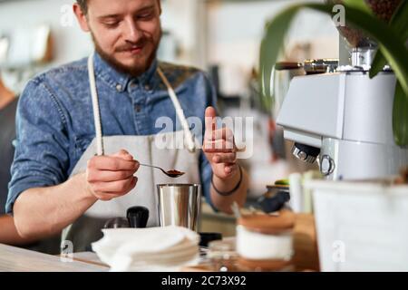Gutaussehender, friedlicher Barista steht auf der Schürze hinter dem Tresen, hält einen kleinen Löffel mit Instant-Kaffee, drückt Zufriedenheit aus, schaut lächelnd weg