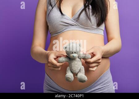Schwangere Frau hält Spielzeug Teddybär, in der Nähe ihres großen Bauch, isoliert auf lila, Nahaufnahme. Spielzeugbär als Symbol für die Mutterschaft und die Geburt von Kindern - Stockfoto