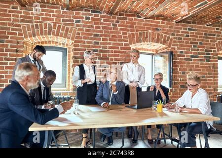 Abteilungsleiter kaukasisch blonde Mann tragen blauen stilvollen Anzug kam Team zu helfen. Zwei Assistenten sind um uns. Kaukasier blonde Frauen tragen weißen Büro shir
