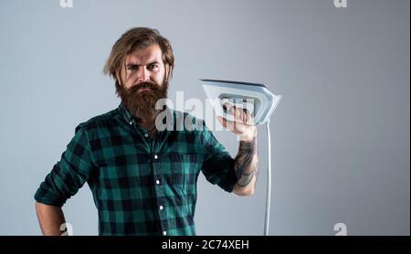 Zimmermädchen für Sie. Mann Bügelkleidung. Mann konzentriert auf Bügeln ein Hemd. Waschküche zu Hause. Kleidung Bügelbrett Haushaltskonzept. Häusliche tägliche Pflicht. Mann Bügeln zu Hause. - Stockfoto