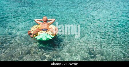 Mann entspannt sich beim Schwimmen auf aufblasbaren Ananas Pool Ring in kristallklarem Meerwasser. Sorgloses Urlaubskonzept. - Stockfoto