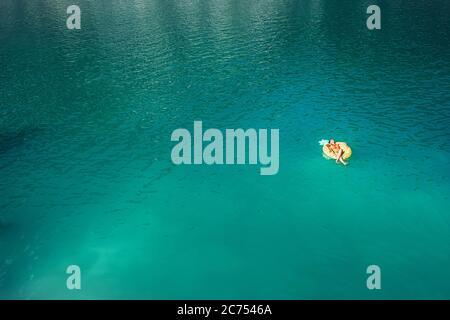 Frau schwimmend auf aufblasbaren Ananasring in Bergsee oben Luftaufnahme. Unbeschwertes Urlaubslebenslang-Konzept Bild. - Stockfoto