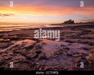 Eine lebendige Sunrise ist in schönen Gezeitenbecken auf Bamburgh Beach mit dem berühmten Schloss mit Blick auf die Szene auf dem Horizont wider.