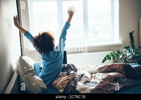 Lockige kaukasische Frau in blauem Pyjama, die sich am frühen Morgen im Bett ausdehnt