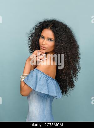 Schöne modische schlanke junge Frau aus Santo Domingo mit langen lockigen schwarzen Haaren trägt subtile Make-up posiert seitlich Blick auf die Kamera ag - Stockfoto
