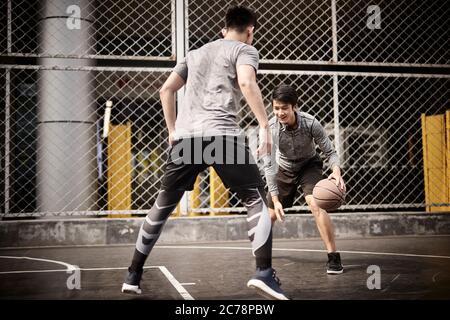 Zwei junge asiatische Erwachsene Männer spielen One-on-One Basketball auf dem Outdoor Court Stockfoto